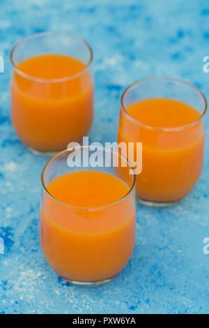 Trois verres de jus de carotte frais sur la masse bleu clair Banque D'Images