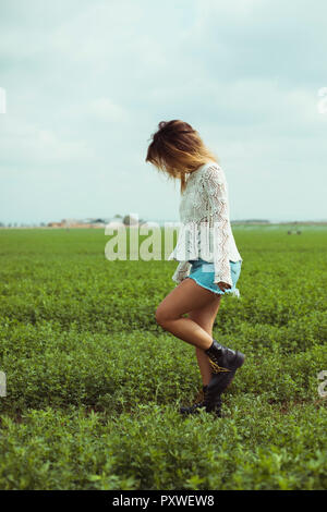 Young woman walking in a green field
