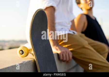 Portrait de deux jeunes hommes avec skateboards assis sur un mur Banque D'Images