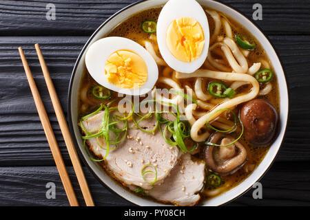 Soupe de nouilles Udon épicé, porc, œufs durs, oignons et champignons shiitake close-up dans un bol sur la table. haut horizontale Vue de dessus Banque D'Images