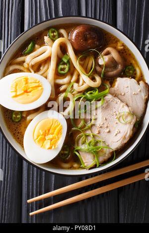 Soupe de nouilles Udon épicé, porc, œufs durs, oignons et champignons shiitake close-up dans un bol sur la table. Haut Vertical Vue de dessus Banque D'Images
