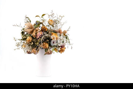 Fleurs séchées dans un vase sur fond blanc Banque D'Images