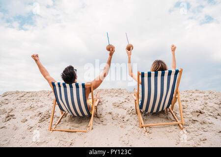 Vue arrière du jeune couple avec des cocktails à la noix de coco vous relaxant dans des chaises longues sur les dunes de sable Banque D'Images
