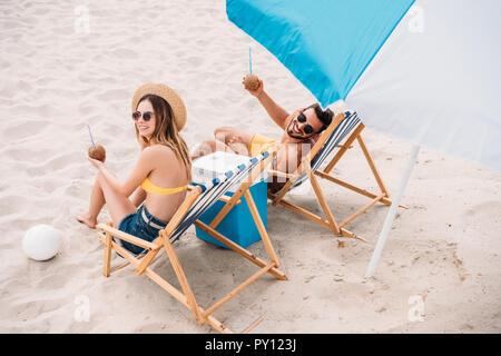 Portrait of happy young couple avec des cocktails à la noix de coco de vous détendre dans des chaises longues sur la plage de sable Banque D'Images