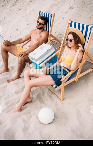 Portrait de la belle jeune couple avec des cocktails à la noix de coco vous relaxant dans des chaises longues sur la plage de sable Banque D'Images