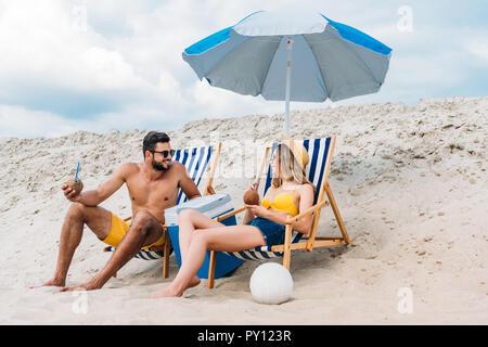 Beau jeune couple avec des cocktails à la noix de coco vous relaxant dans des chaises longues sur la plage de sable Banque D'Images