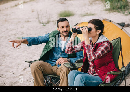 Woman looking through binoculars camping tout en ayant en même temps que mari on sandy beach Banque D'Images
