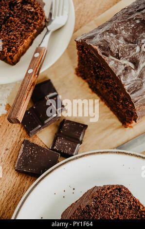 Quatre-quarts au chocolat tranches sur des assiettes blanches. Dans les tons marron, fond de bois. Barre de chocolat en morceaux. Banque D'Images