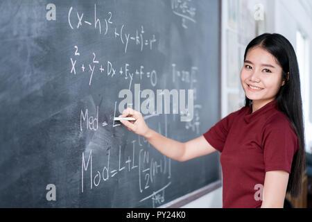 Belle asiatique student writing on blackboard with chalk en classe.