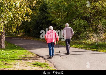 A mature couple faire une promenade le long d'un sentier bordé d'arbres à Teddington Lock,Londres,Angleterre,UK Banque D'Images
