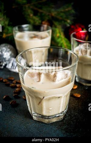 Irish Cream Liqueur cocktail ou boisson traditionnelle de Noël, d'hiver, avec l'arrière-plan foncé rusty branches de sapins de Noël, les grains de café et decorati Banque D'Images