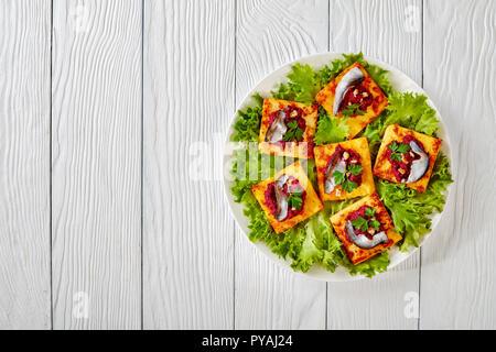 Carrés de polenta frits avec de la purée de betterave crémeux, garni d'anchois sur une plaque blanche sur une table en bois, vue horizontale d'en haut Banque D'Images