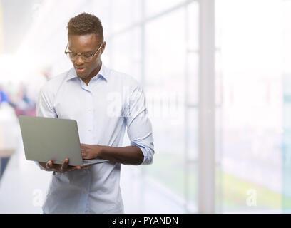 Young african american businessman à l'aide d'un ordinateur portable avec une expression confiante face à la pensée intelligente grave Banque D'Images