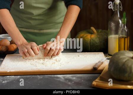 Women's Hands pétrir la pâte. Ingrédients de cuisson sur table en bois Farine de l'huile de lait de citrouille