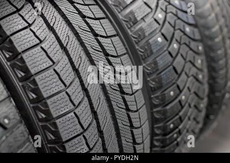 Nouveau pneu de voiture noire, gros plan.Tout nouveau pneus hiver avec une bande de roulement moderne.isolés selective focus.pile de pneus background.saison d'hiver. La texture de la bande de roulement des pneus de voiture.