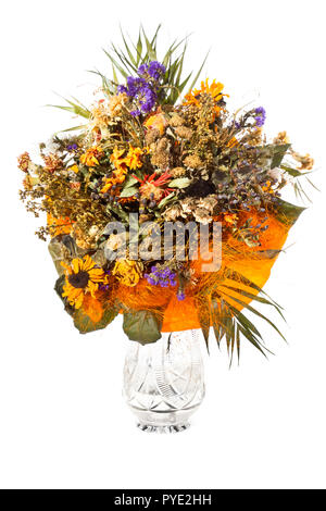 Un gros bouquet de fleurs séchées diverses dans un vase en cristal sur un fond blanc. Banque D'Images