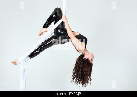 Jeune femme gymnaste dans un costume noir n'astuces sur toile blanche. Banque D'Images