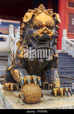 Close up d'une traditionnelle mâle doré lion gardien Impérial avec le symbole du monde qui a eu lieu sous sa patte dans la célèbre Cité Interdite, Beijing, Chi Banque D'Images