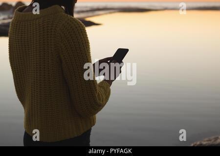 Woman using mobile phone sur la plage pendant le coucher du soleil