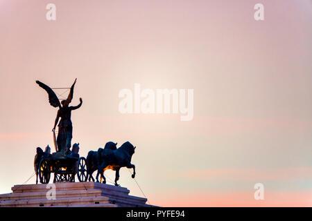 Statue de la déesse Victoria équitation sur quadriga sur le haut du monument de Vittorio Emanuele II au coucher du soleil, Rome, Italie Banque D'Images