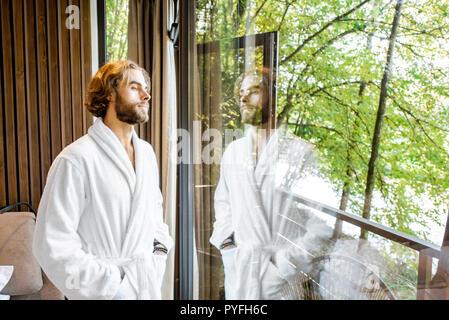 Bel homme en peignoir, debout près de la fenêtre avec vue magnifique sur la forêt dans la chambre d'hôtel moderne