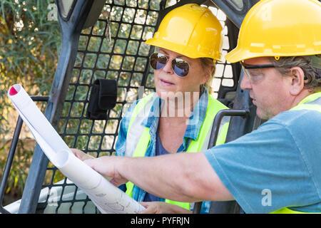 Les travailleurs hommes et femmes avec des modèles techniques Talking at Construction Site Banque D'Images
