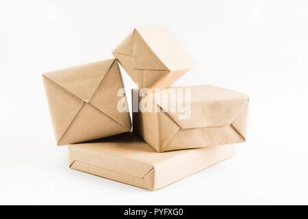 Pile de boîtes enveloppées d'artisanat pour livraison sur fond blanc Banque D'Images