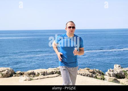 Fit young man jogging sur une piste de course le long de la mer. Remise en forme de loisir sportif dans sportswear bénéficie d'activités physiques sur une journée d'été. Banque D'Images