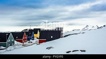 Maisons colorées des inuits le long de la rue couverte de neige, au fjord dans une banlieue de la capitale de l'Arctique Nuuk, Groenland Banque D'Images