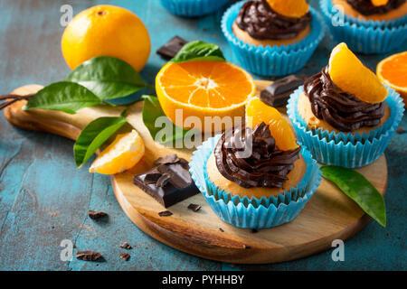 Cupcakes Orange avec crème au chocolat et mandarines fraîches sur une table en béton ou en pierre bleue. Banque D'Images
