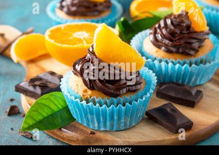 Cupcakes Orange avec crème au chocolat et mandarines fraîches gros plan sur une table en béton ou en pierre bleue. Banque D'Images
