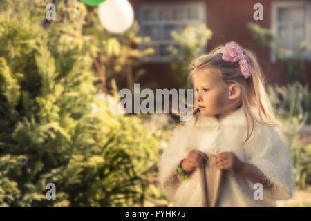 Belle princesse fille enfant mignon dans le manteau extérieur portrait avec soleil vert doux jardin contexte formel heureux concept enfance royale li Banque D'Images
