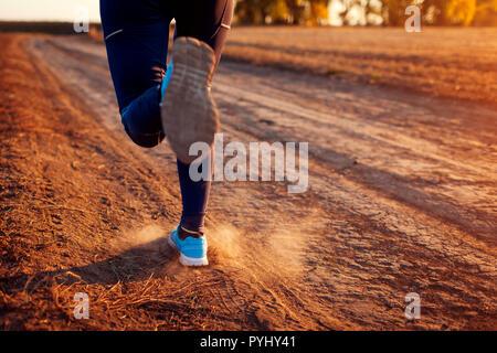 Femme d'exécution dans le champ d'automne au coucher du soleil. Concept de vie sain. Sportifs actifs. Close up de jambes