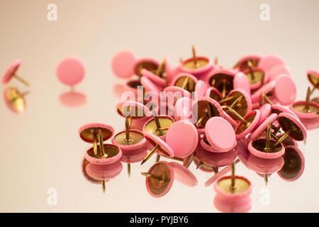 Les punaises roses éparpillés sur une surface réfléchissante Banque D'Images