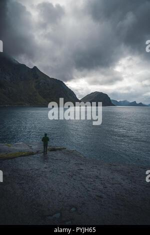 Homme seul, debout devant l'océan atlantique et à la recherche à la mer agitée. Silhouette de marins avec l'homme seul sur les rochers au coucher du soleil Ciel. Ph Banque D'Images