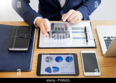 Businessman travailler sur l'analyse financière d'entreprise Bureau Bureau tableaux ou graphiques représentant le calcul de l'impôt l'argent bugget inspecteur prêt faire rapport. Banque D'Images