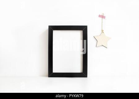 Cadre en bois vierge noire verticale sur le tableau blanc de la maquette. Décoration étoile en bois accroché au mur. Le titre féminin stock photography. Décor à la maison. Hiver Noël concept.