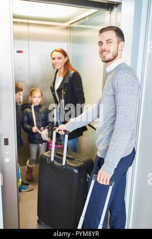 Famille et enfants avec assurance dans l'ascenseur de l'aéroport sur la route des vacances Banque D'Images