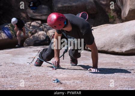 La Pedriza, Madrid, Espagne. Vue aérienne de granite rock climber debout sur ses orteils sur le point de passer la corde par la dégaine de continuer l'escalade. Banque D'Images