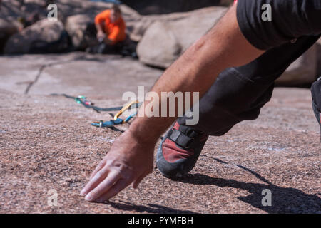 La Pedriza, Madrid, Espagne. Vue aérienne de granite rock climber Mains et pieds alors que l'escalade et de l'assurage partenaire dans l'arrière-plan lointain. Banque D'Images