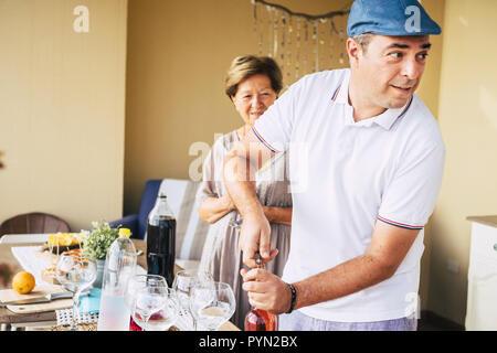 Homme d'âge moyen de l'ouverture d'une bouteille de vin rouge au cours d'un dîner de célébration avec des amis. Femme adultes âgés en contexte msile et attendre que le verre Banque D'Images