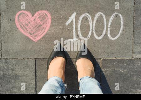 Vue de dessus, les pieds avec texte 1000 aime dans les réseaux sociaux écrits sur trottoir gris Banque D'Images
