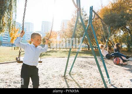 Les enfants voyagent sur une balançoire du parc en automne. L'accent sur le garçon, les filles dans la distance, heure d'or.