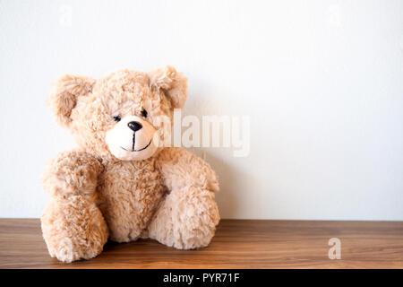 Mignon ours assis seul avec mur blanc sur la table en bois Banque D'Images