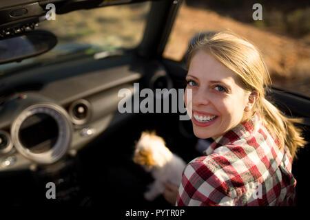 Portrait d'une jeune femme assise dans le siège passager d'une voiture décapotable avec son petit chien.