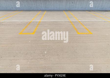Places de stationnement vide avec lignes jaunes dans un parking couvert.