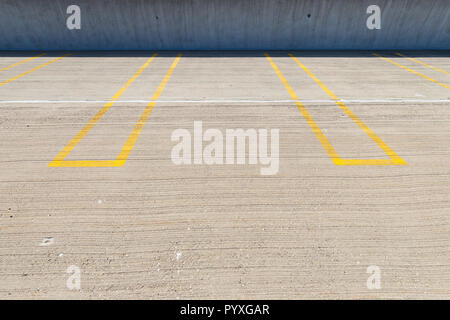 Places de stationnement vide avec lignes jaunes dans un parking couvert. Banque D'Images