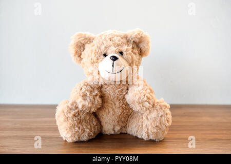 Mignon ours assis seul avec mur de ciment blanc sur la table en bois Banque D'Images