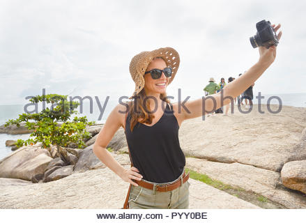 Young woman wearing straw hat selfies en tenant Banque D'Images