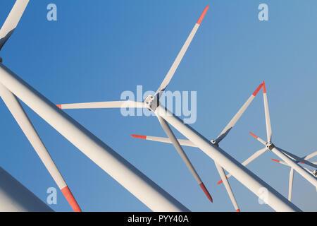 Angle horizontal vue avant d'éoliennes eolian blanc rangée dans une ferme de l'énergie contre un ciel bleu clair Banque D'Images